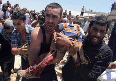 People carry the body of a Palestinian boy, whom hospital officials said was killed in an Israeli air strike on his family's house, in Gaza city