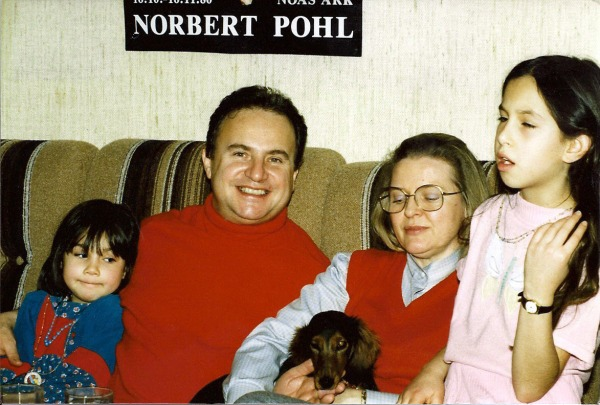 December, 1987. Alison Huguenin holding Pixie. Abbie looking on next to Pierre, Molly standing by Alison
