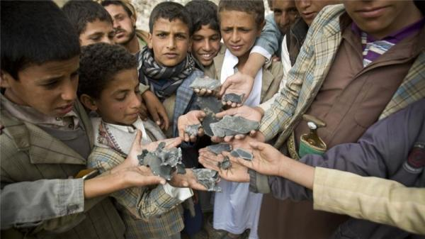 Yemeni boys display shrapnel they collected from the rubble of houses destroyed by air strikes in Yemen near Sanaa